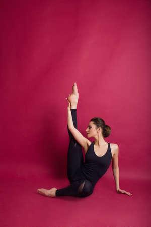 Hermosa mujer delgada y delgada lleva traje de cuerpo negro en estudio aislado en rojo Foto de archivo - 97894215
