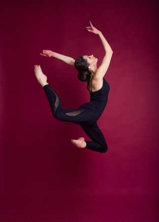 Hermosa mujer delgada y delgada lleva traje de cuerpo negro en estudio aislado en rojo Foto de archivo - 97923503
