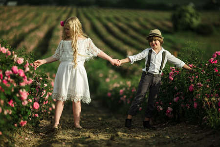 Cute child boy and girl are holding hands are standing in pink rose field. Wearing stylish clothes, summer time