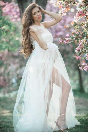 Pregnant pretty woman is wearing white fashion dress posing in pink blossom apple garden, summer time