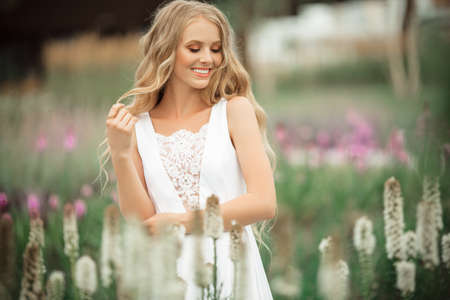 Happy bride is wearing white dress in spring park with purple flowers