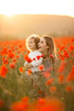 Beautiful smiling child girl with mother are having fun in field of red poppy flowers over sunset lights, spring time