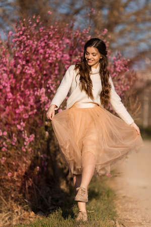 Young beautiful teen girl with perfect skin is wearing romantic clothes posing near blossom tree in cherry garden Stockfoto