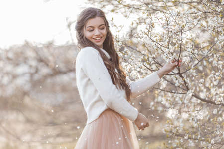 Pretty smiling teen girl are posing in garden near blossom cherry tree with white flowers. Spring time