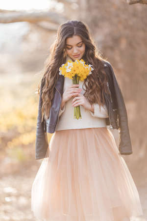 Pretty smiling teenager girl are holding bouquet of narcissus flowers in park over sunset lights. Spring time