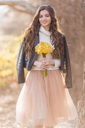 Pretty smiling teen girl are holding bouquet of narcissus flowers. Spring time