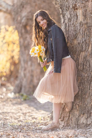 Portrait of smiling teenager girl are wearing casual clothes holding bouquet of narcissus flowers in park over sunset lights. Spring time Stock Photo