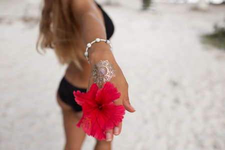 Young tanned woman with perfect body with golden tattoo on her hand and red flower is walking on the beach. Beauty and fashion concept. Banco de Imagens