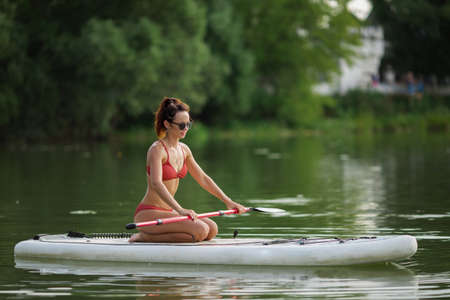Young pretty fitness girl in swimwear is paddling on a SUP in the middle of the lake with a green forest in the background.