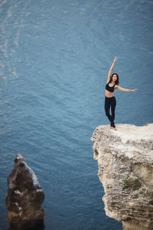 Beautiful slim woman practices yoga and pilates on the cliff of mountain with the sea view. Sportive and heathy lifestyle concept.