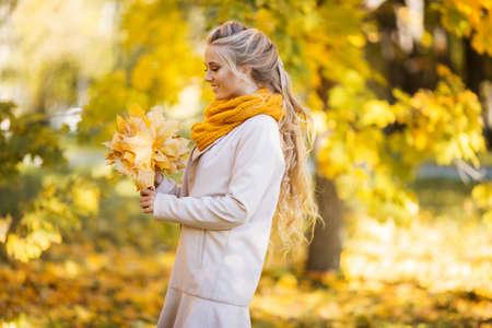 Chica adolescente bastante rubia está caminando en el parque otoño con hojas amarillas Foto de archivo