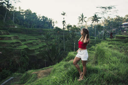 Pretty woman in tegalalang rice terrace fields in morning sunrise, Ubud, Bali, Indonesia.
