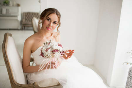Young bride in a beautiful dress holding a bouquet of flowers in bright white studio. Wedding concept. Standard-Bild