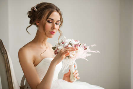 Close up portrait of young bride in a beautiful dress holding a bouquet of flowers in bright white studio. Wedding concept.