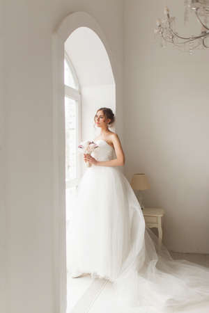 Young bride in a beautiful dress holding a bouquet of flowers posing near window in bright white studio. Wedding concept.