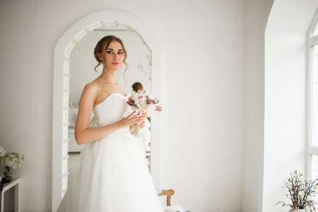 Young bride in a luxury dress holding a bouquet of flowers in bright white studio. Wedding fashion concept.