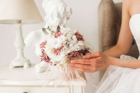 Young bride is wearing beautiful dress holding a bouquet of flowers in bright white studio. Wedding concept.