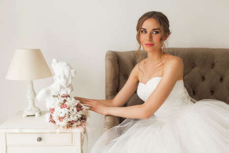 Young bride in a beautiful dress sitting at home with nice white interior. Wedding concept.