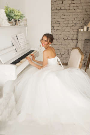Young bride in a beautiful dress is playing piano in bright white studio. Wedding concept. Standard-Bild