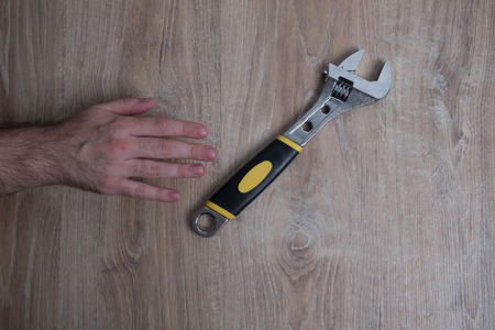 Adjustable wrench studio image. Mans hand reaches for a wrench. Tool adjustable wrench with the rubber handle on a blurred wooden background.