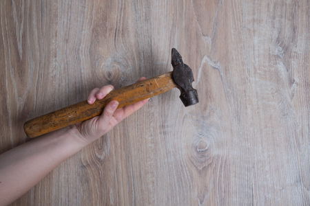 Hammer studio image. Female hand holding a hammer. Hammer tool on blurred wooden background.