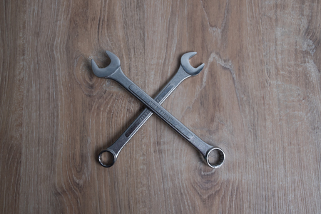 Set of wrenches studio image. Tool crossed old spanners on a wooden background.