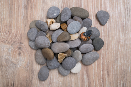 A bunch of sea stones. River stones on a wooden background. Smooth stones. Archivio Fotografico - 124982881