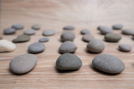 Sea stones arranged in rows. River stones on a wooden background. Smooth stones. Archivio Fotografico - 124982883