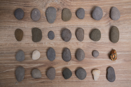 Sea stones arranged in rows. River stones on a wooden background. Smooth stones. Archivio Fotografico - 124982888