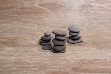 Sea stones on top of each other. Pyramid of river stones on a wooden background. Columns of small smooth stones. pillars. Archivio Fotografico - 124982894