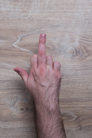 Male hand the gesture of the fuck. Hand shows a fuck sign. Hand on wooden background.