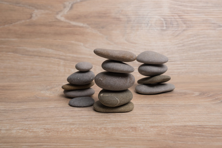 Sea stones on top of each other. Pyramid of river stones on a wooden background. Columns of small smooth stones. pillars. Archivio Fotografico - 124982897