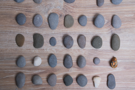 Sea stones arranged in rows. River stones on a wooden background. Smooth stones. Archivio Fotografico - 124983117