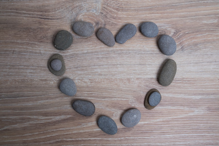 Heart lined with sea stones. River stones in the shape of a heart on a wooden background. Imagens