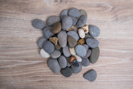 A bunch of sea stones. River stones on a wooden background. Smooth stones. Archivio Fotografico - 124983136