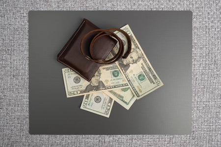 Dollar bills on gray background. Mens leather wallet with dollar bills. Leather bracelet casual. Stock Photo