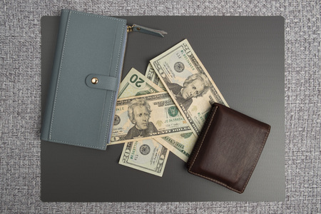 Dollar bills on gray background. Mens leather wallet with dollar bills. Womens gray leather wallet. Stock Photo