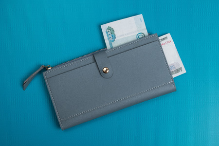 Womens leather wallet studio image. Gray womens wallet with banknotes. Ruble bills. Rubles in wallet.