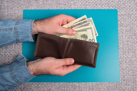 Male wallet with banknotes. Studio image. Mens hands hold a leather wallet with dollar bills.