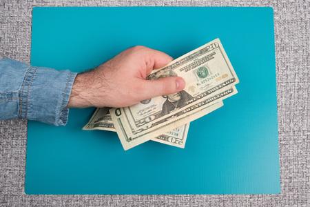Dollar bills studio image. Male hand holds dollar bills. Money in the male hand. Stock Photo