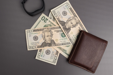 Dollar bills on gray background. Mens leather wallet with dollar bills. Electronic clock on the money.