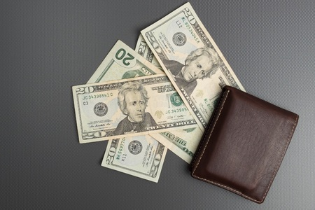 Dollar bills on gray background. Mens leather wallet with dollar bills.