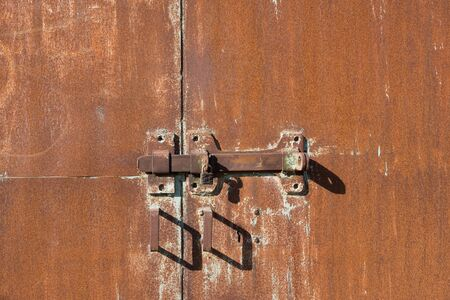 Background of old iron rusty gate. Metal gate with red rust. The texture of a rusty gate with a hinged and padlock lock. Gates with door handles. Imagens