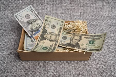 American dollars in a carton box. Piggy bank with dollars. Money in the box.
