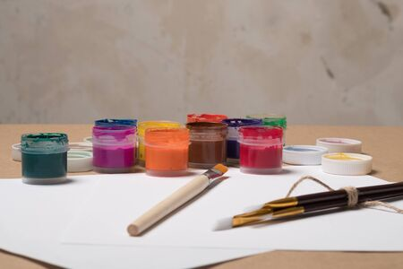 Paints for painting with brushes on a white sheet. Acrylic paints in tubes. Old paint in bottles. Paint brushes for painting and a blank white sheet of paper for text. Stok Fotoğraf