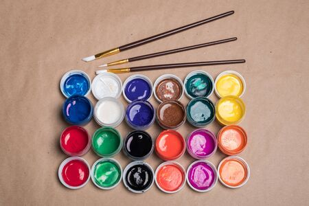 Set of paints for painting with brushes. Acrylic paints in tubes. Old paint in bottles. Paint brushes for painting.