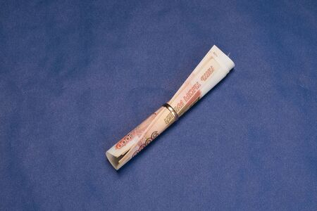 Russian money with a wedding ring. Russian rubles. Russian money bills on blue background.