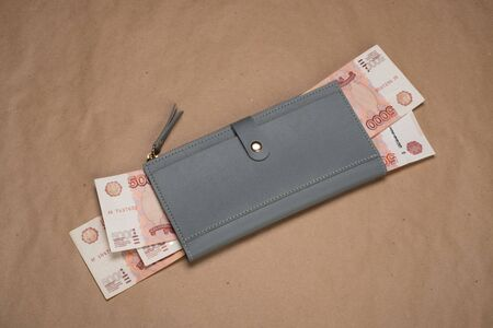 Russian money in a wallet studio image. Women's wallet with Russian rubles. Russian money bills in a gray wallet.