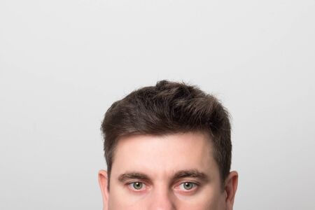 Man with gray-green eyes and beautiful hair. Brunette man with gray eyes. Фото со стока