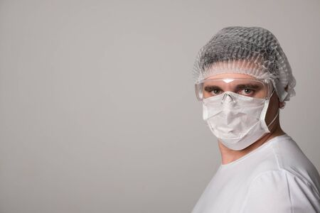 Male doctor in a surgical mask and glasses. Surgeon before the operation. Young man in a medical mask. Фото со стока